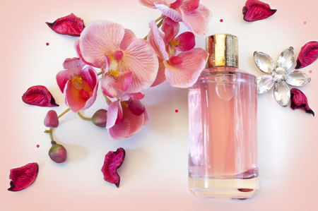 bottle of womens perfume and a delicate orchid flower on a pink background