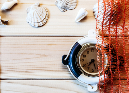 Decorative marine clock and shells on the background of wooden boards