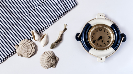 Decorative marine clock and shells on a white background