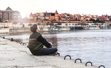 stroll: Stylish young man sitting near a Rivers on the waterfront  Stock Photo