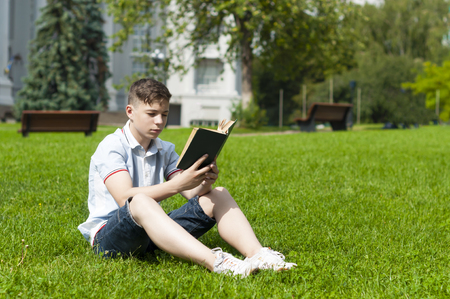 Student reading book sitting on green grass Stock Photo