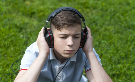 Pensive Young man with headphones listening to music Stock Photo