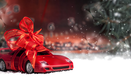 small car with red decorative bow in snow
