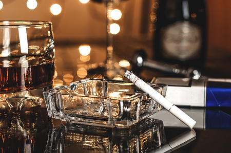 cigarette pack: glass with whiskey and crystal ashtray on the table in the bar