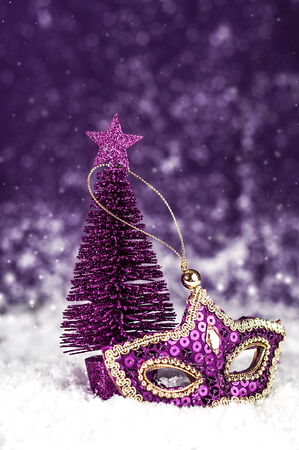 Christmas tree, purple carnival mask with sparkles on a snowy background