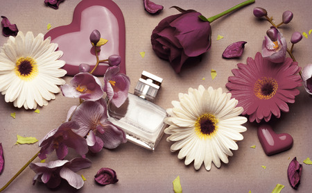 bottle of women's perfume, flowers on light brown background