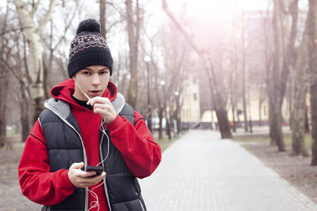 sporty young man with mobile phone in city park