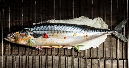 raw fresh mackerel stuffed with lemon on an iron grate Stock Photo