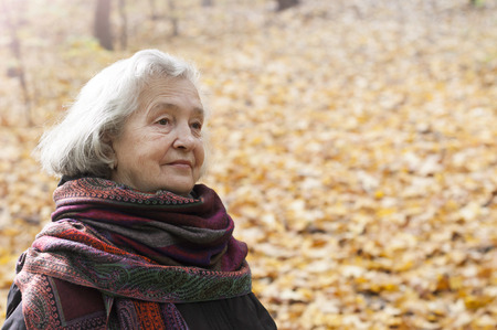 Elderly woman walking in a park in autumn afternoon Stock Photo