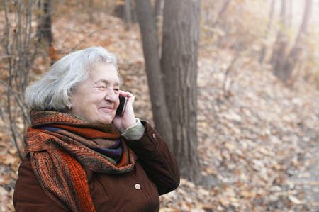 Elderly woman talking on the phone in an autumn park