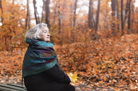An elderly woman sitting on a bench in a park in an autumn afternoon
