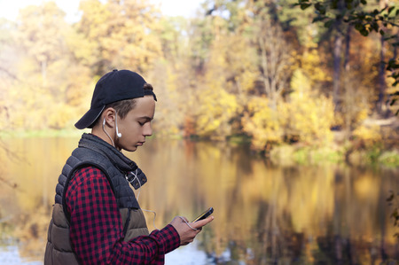 sad young man writes a message in an autumn park