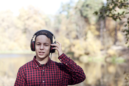 young man in headphones listening to music in autumn park