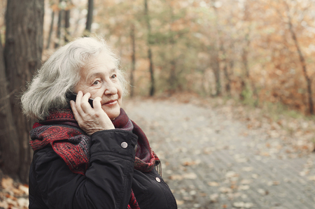 elderly woman talking on the phone in an autumn park, during a walk