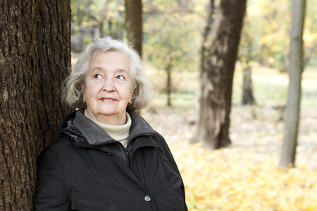 elderly woman on a walk in a park in autumn afternoon