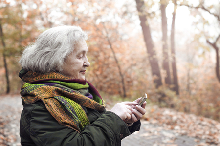 elderly woman on a walk in an autumn park with a mobile phone