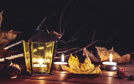 candles, old lantern, autumn leaves on a wooden table
