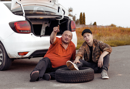 father and son rest during wheel replacement