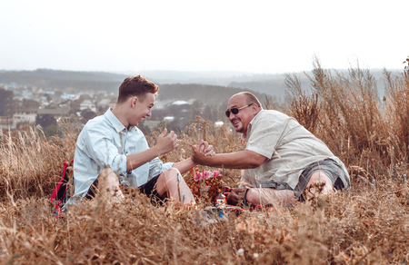 happy father and son resting on nature in the evening, handshake Stock Photo