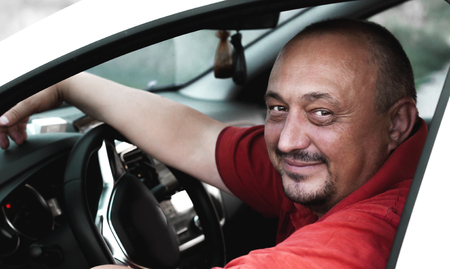 positive attractive man sitting behind the wheel of a white car Stock Photo