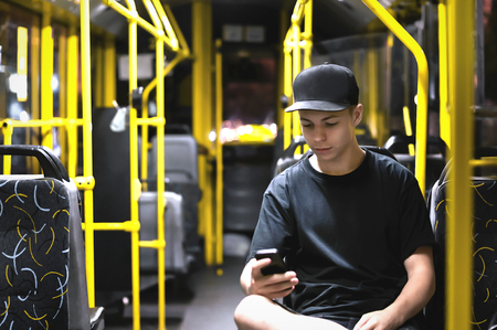 young man reading a message in a public transport in the evening