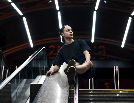 stylish Young man sitting on the handrails of an escalator