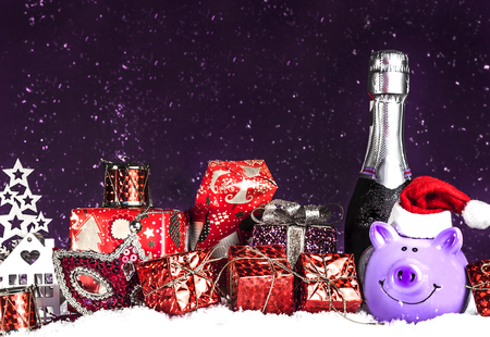 bottle of champagne, Christmas gifts on a dark purple background Stock Photo