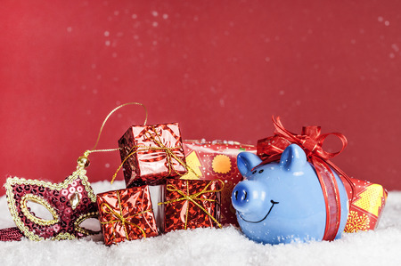 blue pig with a red bow in the snow, mask, gifts
