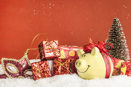 yellow pig with a red bow in the snow, mask, gifts Stock Photo