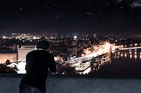 young man standing on the roof of a building, looking at the night city Stock Photo