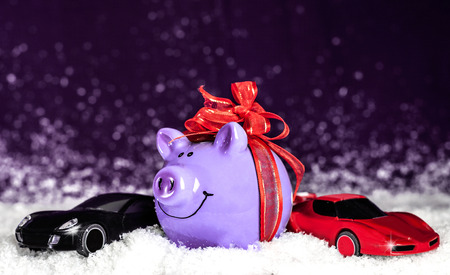 Purple pig with a red bow, miniature cars in the snow Stock Photo