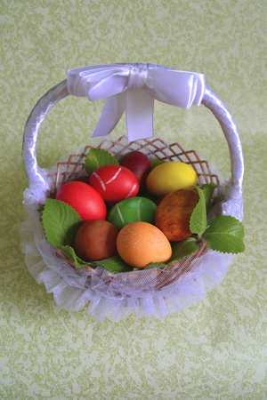 colored dye: Easter colored dye chicken eggs in a wicker basket from vines with branches mint