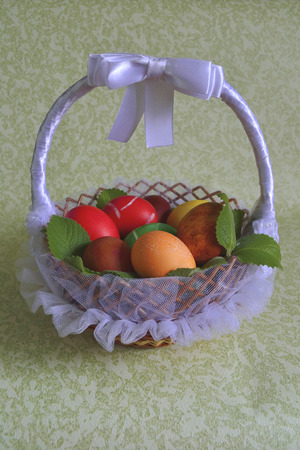 twined: Wicker from a vine basket with Easter chicken eggs colored dyes on the mint branches