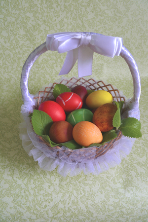twined: Easter egg painted paints in a wicker basket on mint branches Stock Photo