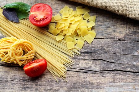 Three different types of pasta with fresh purple and green basil and red tomatoes on a wooden background with a place for text. Traditional Italian pasta. Top view. Copy space. 写真素材