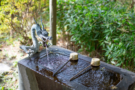 The Water Purification Basin temizuya or chozuya in Japanese temple. The cleansing hands and mouth ritual in Japanese temple or shrine. The dragon fountain.