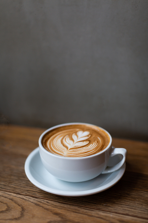 A beautiful cup of cappuccino with latte art in the loft space background. Trendy toning. Minimal composition, hipster vibes. Side view, copy space for your text.