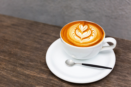 Close up of beautiful large cup of cappuccino with trendy heart shape latte art. Summer loft urban cafe. Outdoor drinking coffee. Fashionable coffee set and cutlery. Copy space for your text.