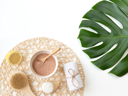 Moroccan red clay powder in the white plate, towel. Ingredients for home skin care, easy spa procedures and detox. Decorated with monstera leaf. Minimal composition. Fashion and beauty blog. Stock Photo