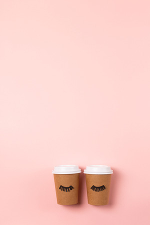 Two craft cups to do on the pastel pink background. Decorated with funny cute paper eyes. Wake up and drink coffee concept. Flat lay. 写真素材
