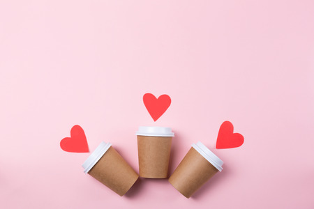 Row of three brown craft cups of coffee or tea to go on the pastel pink background. Flat-lay, top-view. Decorated with red paper hearts. Copy-space.