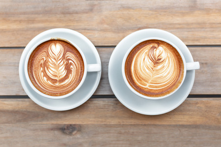 Two beautiful cups of cappuccino with trendy latte art in the wooden space background. Minimal composition, hipster vibes. Top view, flat-lay.