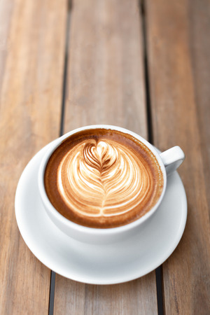 A beautiful cup of cappuccino with trendy latte art in the wooden space background. Minimal composition, hipster vibes. Side view. Copy space for your text. Stockfoto
