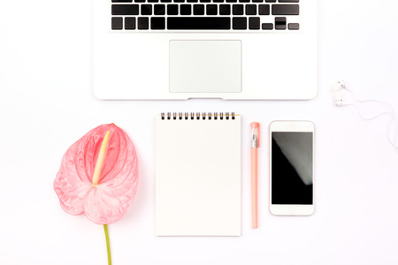 Feminine workspace background with stationery, a smartphone and pink flamingo flower. Flat-lay, top view. Copy space for your text.