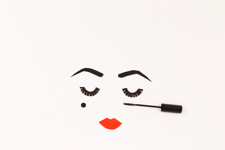 Paper made woman face with make up. Red lips, bold eye brows, long lashes and beauty spot. Copy space for your text. Top view, flat lay. Banco de Imagens