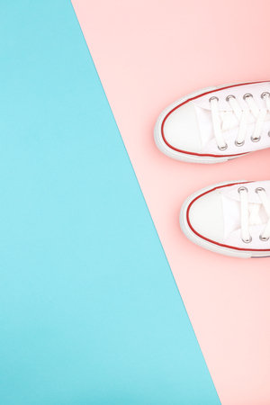 White sneakers on the pastel pink and blue background. Trendy colors. Copy-space for your text. Flatlay, top view. Stock Photo