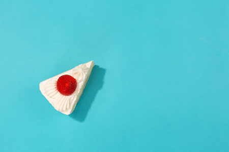Japanese style strawberry shortcake on vibrant blue background. Flat-lay, top view. Copy space for your text.