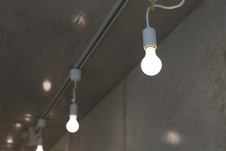 Incandescent light bulb and concrete wall. Loft design details. Trendy interior background