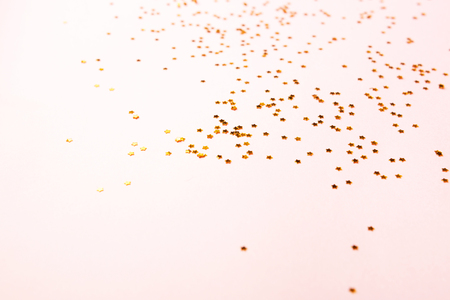 Golden star shaped confetti scattered on pastel pink background. Holiday and festive vibes. Christmas, New Year and Birthday concept. Cpy space for your text.