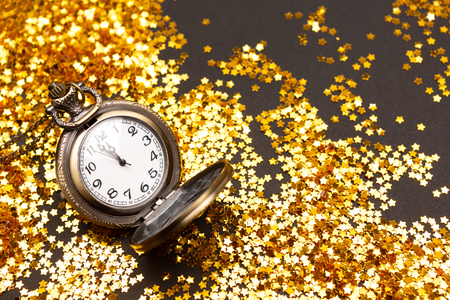 Vintage clock shows almoust midnight. Decorated with confetti. New Year countdown concept. Flat-lay, top view. Copy space for your text.